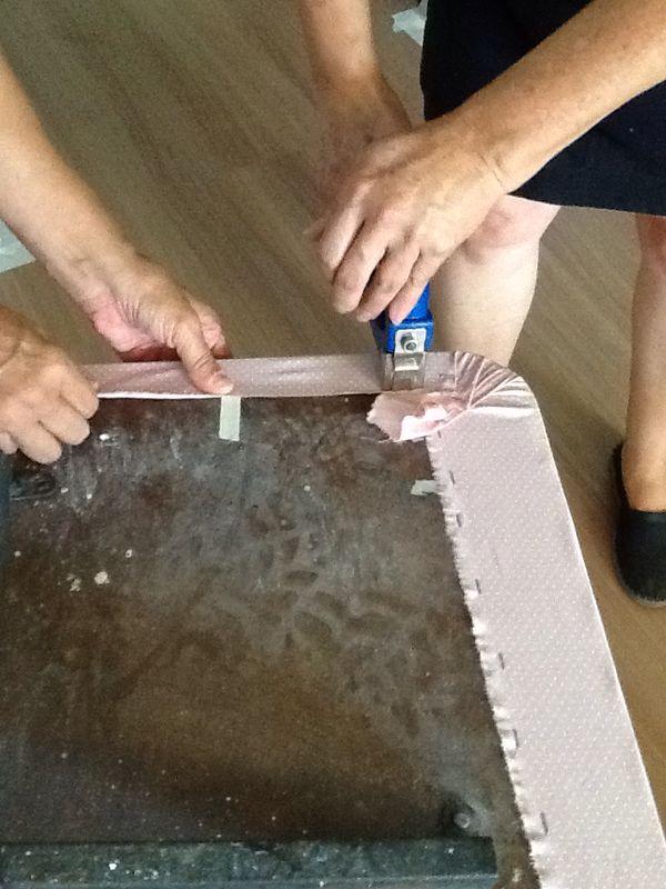 Passo 9: Com uma rocama, pregue a sobra do tecido na parte inferior do tampo.